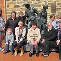 Image: family group pose with sculpture