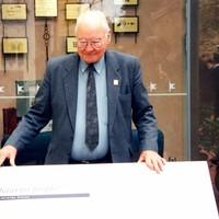 Image: elderly man standing behind large graphic plaque