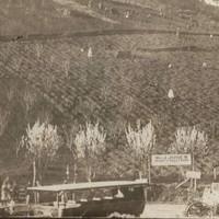 Image: old car in front of sign on hillside