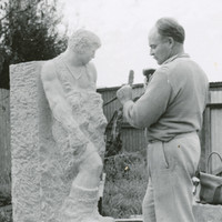 Image: black and white photograph of man sculpting in stone