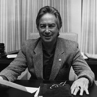 Image: Black and white photograph of a smiling man in jacket sitting at his desk holding a sheet of paper