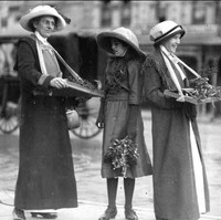 Image: Three women and a young girl wearing hats and long coats stand in the street holding sprigs of wattle plant