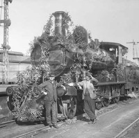 Image: Front view of a train decorated in foliage, two men stand at the front of the train