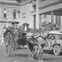 Image: Two women and a child sitting in a buggy drawn by a single horse through a city street