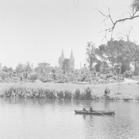 Image: Two men sitting in a row boat on a River, with a park and Cathedral visible in the background