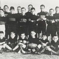 Image: a group of boys in football uniforms with their teacher. The boy seated in the centre of the front row holds a football with