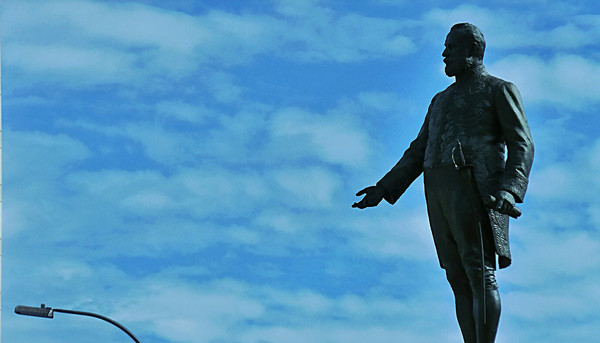 Image: sculpture of standing man silhouetted in sky