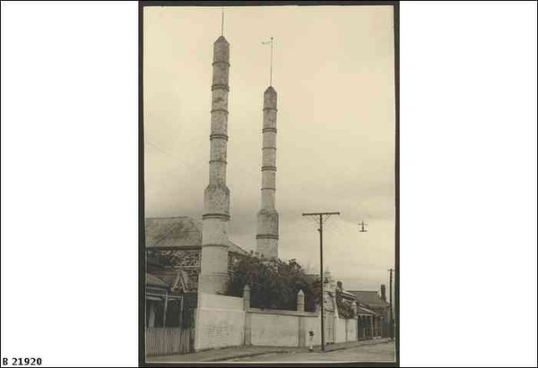 Image: two minarets front a mosque partially obscured behind a high wall and trees