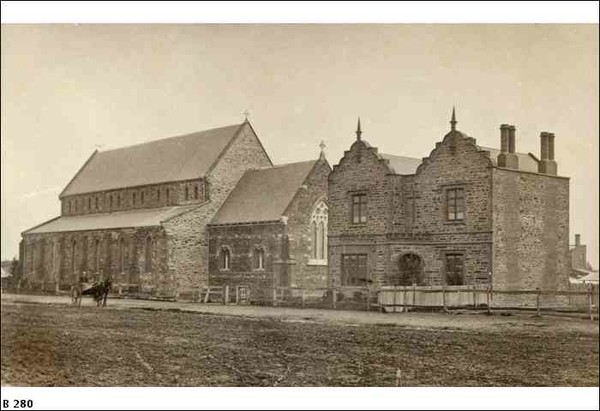 Image: a stone church with a clerestory roof sits along side a two storey rectangular stone building with two gable roofs with scalloped ends topped with finials on the street side.