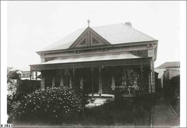 Image: A symmetrical fronted bluestone villa with decorative wrought iron verandah, tin roof and decorative gable end with finial centred above the front door sits in a established garden with a number of flowering bushes.