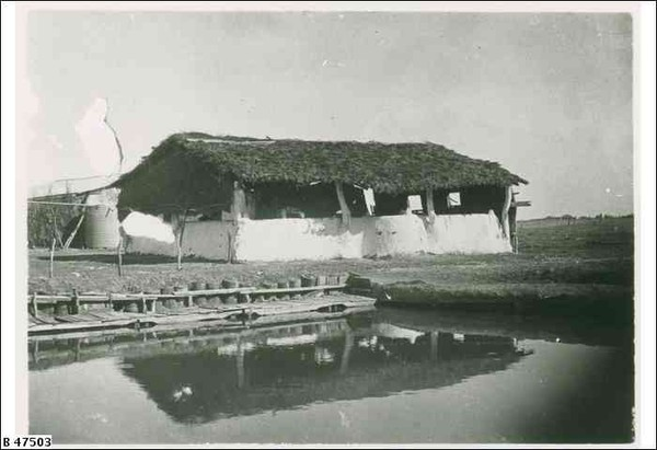 Image: A wooden framed building with a thatched roof and half height mud-brick walls stands behind a square edged pool in a barren field