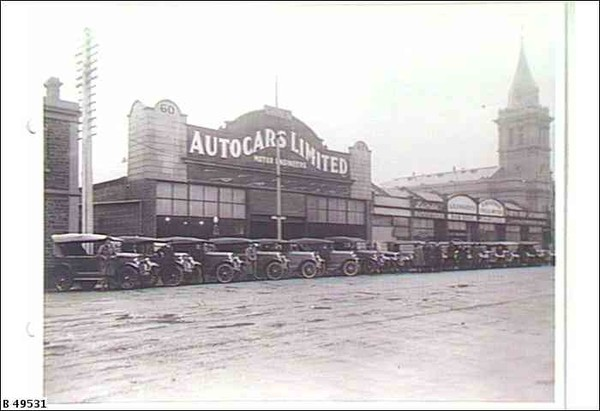 """Image: a row of 1920s era cars are parked on a 45 degree angle facing a dirt road. Behind them is a single storey commercial building, part of a row of terraced shops, with a curved parapet and a sign which reads """"Autocars Limited""""."""