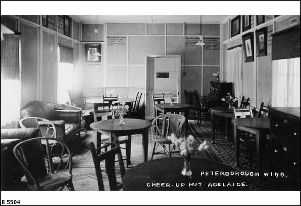 Image: a black and white photograph of a lounge with leather couches and wooden chairs set around tables. There are vases of flowers on the tables and pictures in frames on the walls.