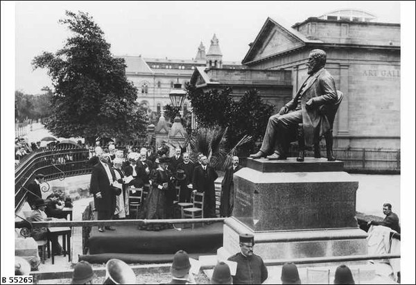 Image: crowd of people around large bronze statue of seated man