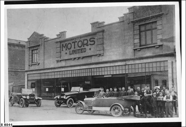 """Image: a group of men in early 20th century clothing pose around a number of cars parked outside a two storey building with a sign reading """"Motors Limited"""""""