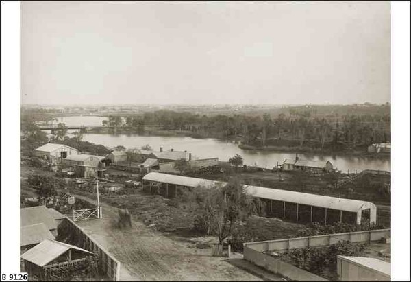 Image: a collection of stable buildings on the bank of a river.