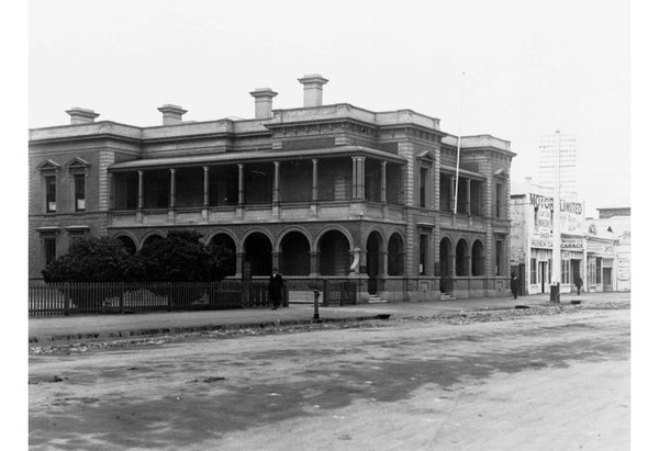 Image: a stone manse with a low pitched roof mostly hidden behind a parapet, an arched return verandah and columned balcony, and rectangular windows with triangular pediments.