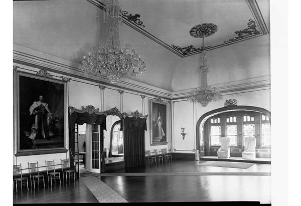 Image: A large, well-lit open room with wooden floors, crystal chandeleirs and large portraits hanging on its walls