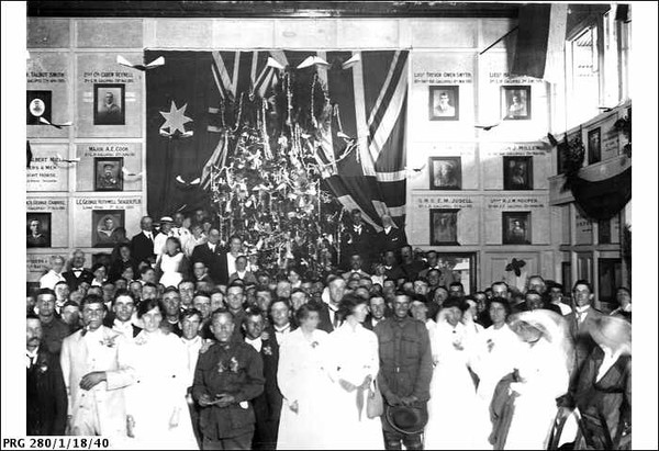 Image: A large group of men and women stand in front of a decorated Christmas tree
