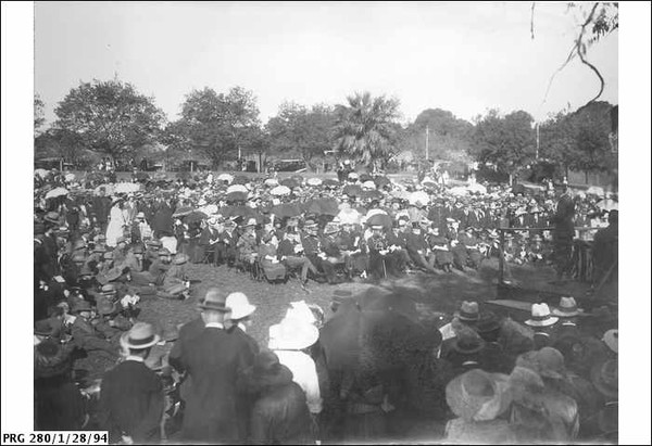 Image: a large crowd of people in 1920s dress, some with umbrellas, sit or stand in a park around a man on a low stage
