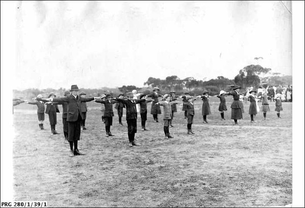 Image: a group of boys and girls in early 20th century clothing and hats stand in lines in a field with their arms outstretched to either side.