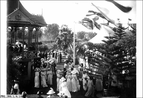 Image: A crowd of women in white dresses and men in dark suits circa 1912 stand in a park around a rotunda upon which a band plays. The rotunda is draped in an Australian flag while other flags fly nearby. In the background a large marquee can be seen.