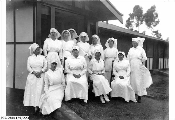 Image: 12 women wearing white dresses and nurses veils are arranged in two rows, the back eight women standing, the front four sitting in this posed photograph.