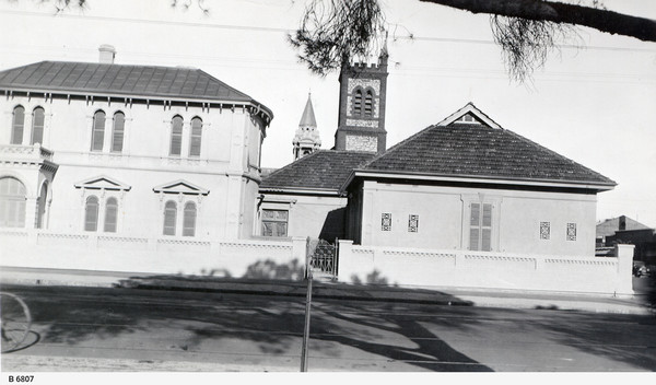 Image: street view of a white stone mansion with an additional building adjoined and two church towers in the background.