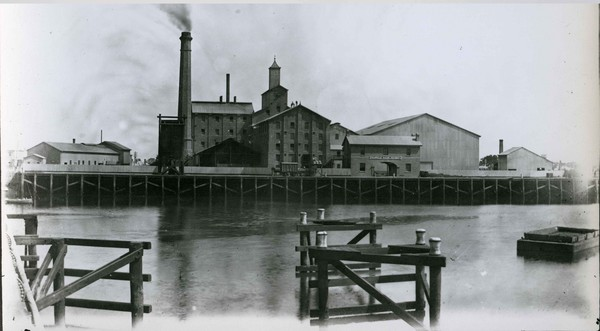 Image: View across river of large brick buildings and chimney with smoke