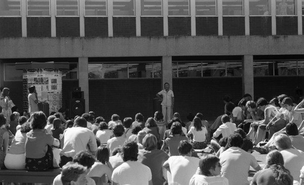 Image: A man in white stands with a microphone in front of a group of seated students