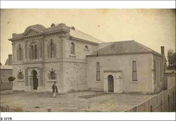 Image: A man in a top-hat and Victorian clothing stands in front of a large, two-storey rectangular stone building