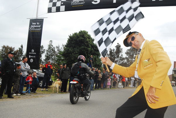 Image: man waving checkered flag as motorbike rides away