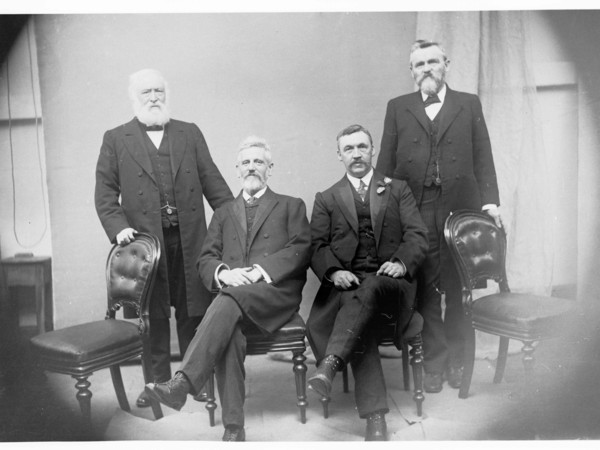 Image: A group of middle-aged men in Edwardian attire pose for a photograph. The two men in the centre sit on chairs, while the other two stand on either side of the group