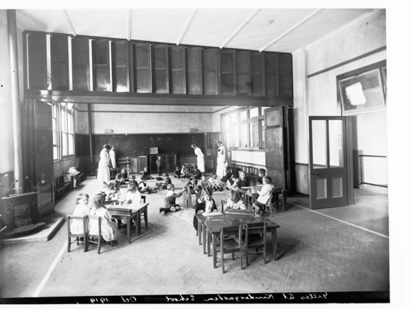 Image: A group of small children play in a large open room while four female teachers in Edwardian attire look on