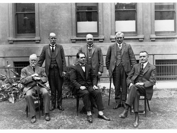 Image: Six men in suits pose for a photograph in front of a large building. Three men are seated in the front row, while the remainder stand in another row behind
