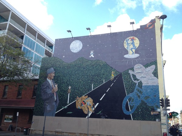 Image: mural of an older man with an ice cream cone watching an abstract figure and a boy both riding bikes on a road in the moonlight. Above, two aliens are on an unidentified flying object