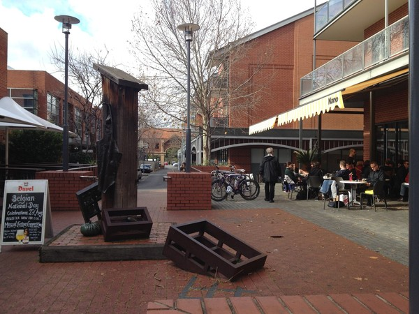 Image: bronze sculpture of column with apron in a brick courtyard of restaurants' patios