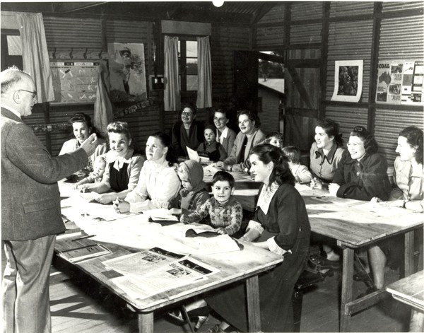 Image: man standing in front of group of women and children sitting at desks
