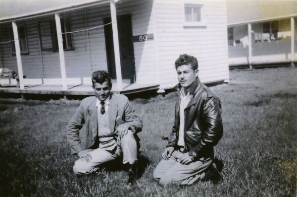 Image: two men kneeling on grass in front of buildings