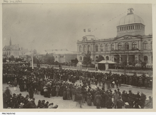Image: A large group of people in 1880s dress stand in distinct lines in front of a large building with a domed roof which is decorated with flags and bunting.