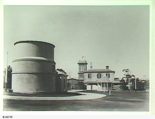 Image: large funnel like building with two story building in background
