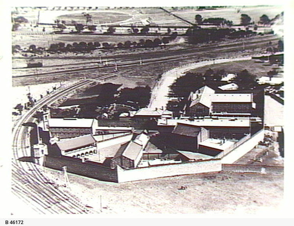 Image: an aerial photograph of a prison arranged in a half octagonal panopticon style. With long rectangular cell blocks inter-spaced with triangular paved yards. A high wall surrounds the buildings.
