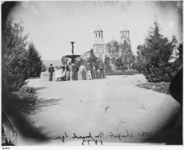 Image: Two young girls and a row of young men are leaning against a fountain in front of a church
