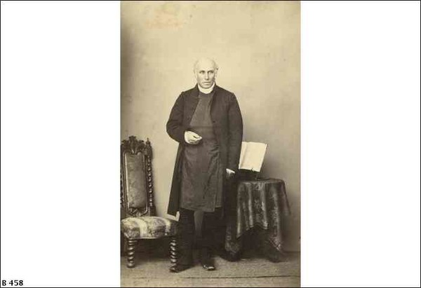 Image: Sepia photograph of bald man standing in front of a chair and table