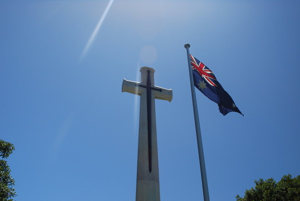 Image: Australian flag in front of cross monument