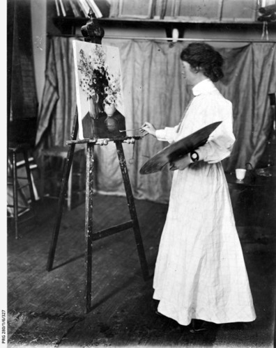 Image: A young Caucasian woman in a full-length Edwardian-era dress paints a still life on an easel. The painting features a couple of vases holding flowers