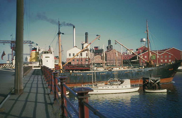 Image: A modern steel-hulled vessel passes through the centre of an historic swing bridge. Another modern boat is moored next to the bridge, and a large complex of historic industrial buildings are visible in the background