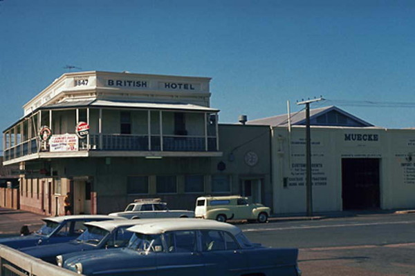 Image: A cream coloured two-storey building with second-floor verandah. Two cars are parked in front of the building and a man stands near its front door