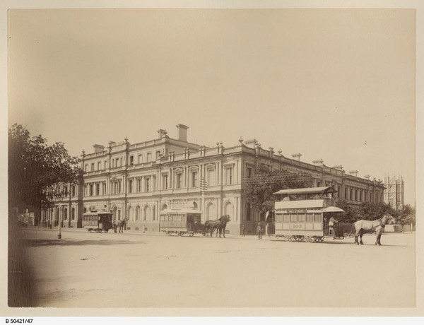 Image: Horse-drawn trams in front of ornate building facade