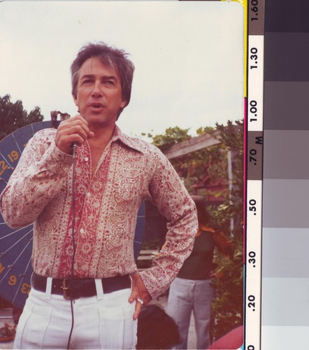 Image: Man in pink paisley shirt and white trousers speaks into a microphone